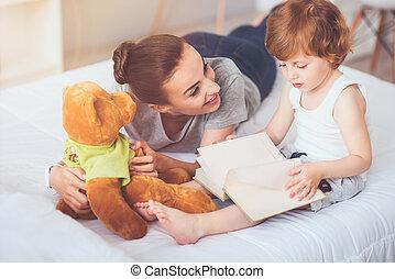 Joyful mother teaching her son to read.