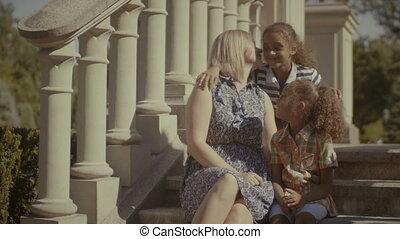 Joyful multi ethnic family resting on stairs - Joyful loving...