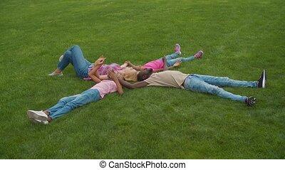 Joyful multiethnic family lying on grass in circle - Joyful ...