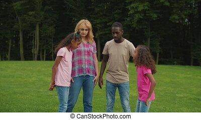 Joyful multiethnic family with girls stacking hands - Joyful...