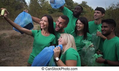 Close-up of smiling multinational ecology activists with full trash bags posing for selfie shot among forest. Happy diverse people rejoicing at well-done teamwork to rid forest from plastic garbage