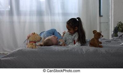 Joyful multiracial kids having fun on the bed