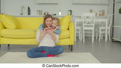 Joyful mum and daughter watching cartoons on phone - Joyful...