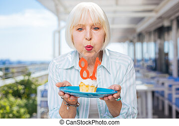 Joyful nice aged woman making a wish