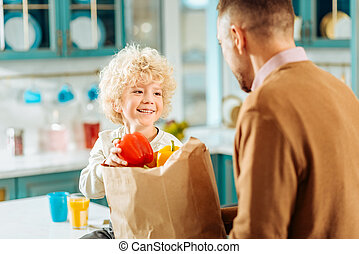 Joyful nice boy taking a pepper from the bag
