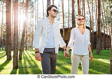 Joyful nice couple walking in the woods