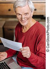 Joyful nice man working at the laptop