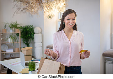 Joyful nice woman holding her shopping bags