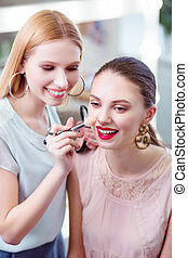 Joyful nice woman touching her clients nose with a brush