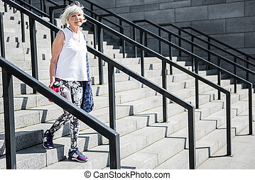 Joyful old lady returning home after training down steps outside