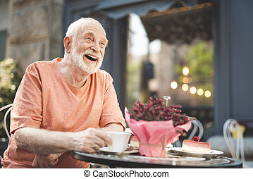 Joyful old man laughing in delight outside