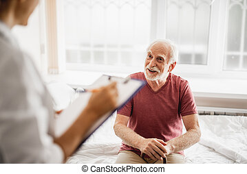 Joyful old man sitting on hospital bed and chatting with doctor