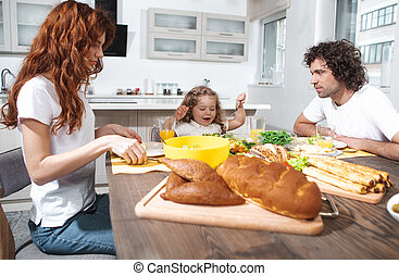 Joyful parents and daughter eating healthy food in kitchen