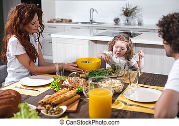 Joyful parents and girl dining together in kitchen