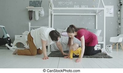 Joyful parents crawling together with baby indoors