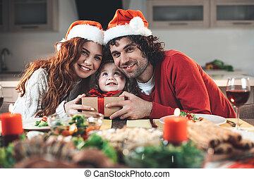 Joyful parents having fun with daughter on celebration