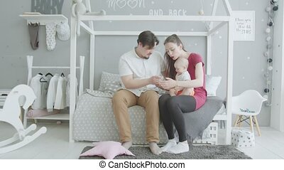 Joyful parents playing with baby girl in bedroom