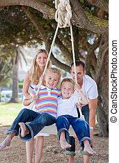 Joyful parents pushing their children on a swing