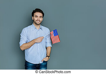 Joyful patriotic man holding the US flag