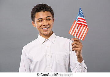 Joyful patriotic man looking at the US flag