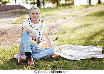 Joyful pensioner having picnic in the park