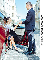 Joyful polite man helping a woman