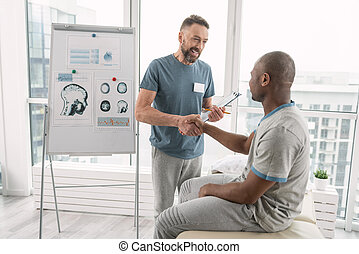 Joyful positive doctor shaking his patients hand