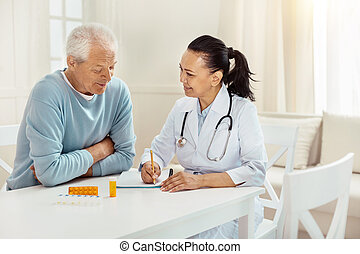 Joyful positive doctor taking notes