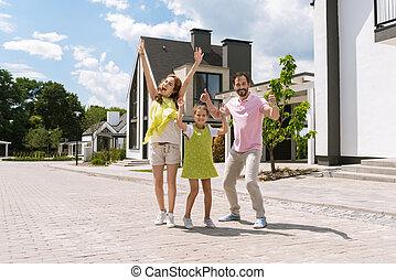 Joyful positive family holding their hands up