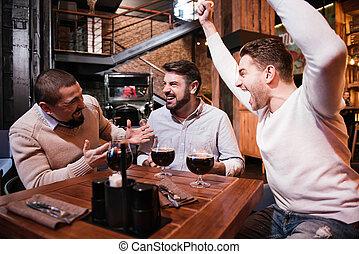 Joyful positive man cheering with his friends