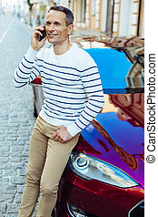 Joyful positive man having a phone conversation