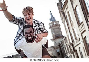 Joyful positive man having fun with his friend