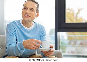 Joyful positive man holding a cup