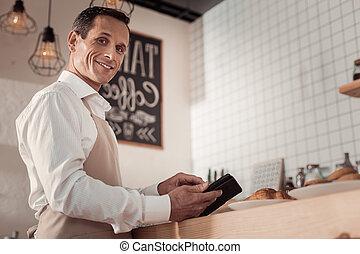 Joyful positive man running a business