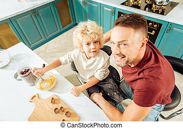 Joyful positive man sitting together with his son