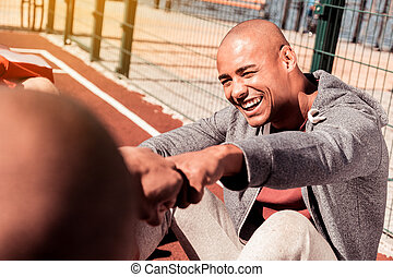Joyful positive man touching his friends hand
