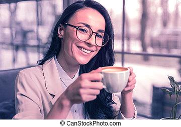 Joyful positive nice woman enjoying her drink