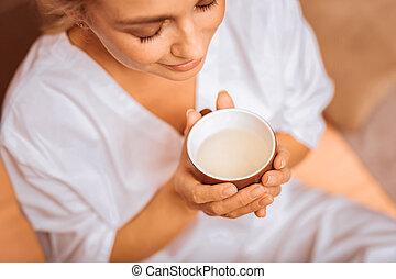 Joyful positive woman enjoying her herbal tea