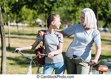 Joyful positive woman hugging her granddaughter