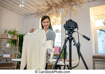 Joyful positive woman showing her while pullover