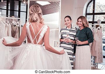 Joyful positive women looking at the bride