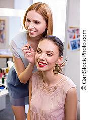 Joyful positive young woman enjoying her eyelashes