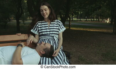 Joyful pregnant couple bonding in public park