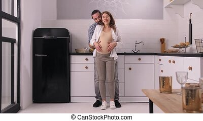 Happy husband and pregnant woman talking fun, cuddling and caressing big belly while spending free time at home. Smiling couple expecting baby enjoying hugs, touching and conversation in cozy kitchen
