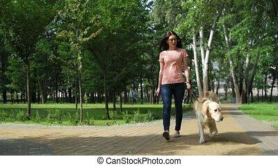 Joyful pretty woman walking with her dog