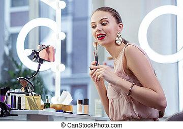 Joyful pretty young woman showing makeup tutorial