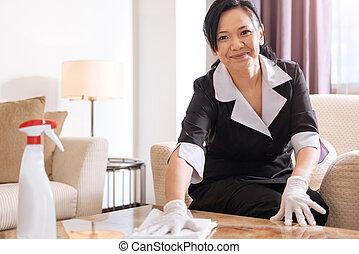 Joyful professional hotel maid sitting in the armchair -...