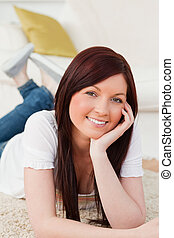 Joyful red-haired woman posing while lying on a carpet