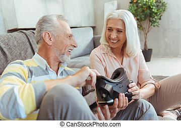 Joyful retired couple testign a new VR device