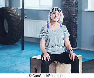 Joyful retired lady resting on wooden box in fitness club